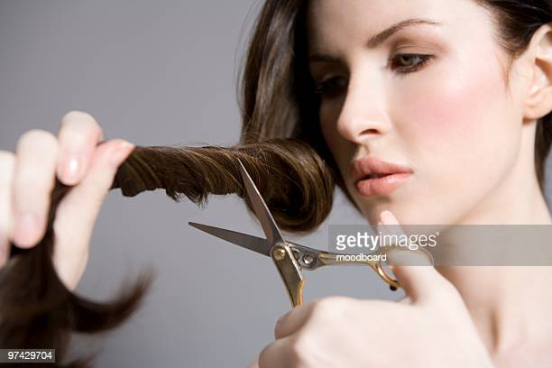 woman cutting long brown hair - cutting stock pictures, royalty-free photos & images