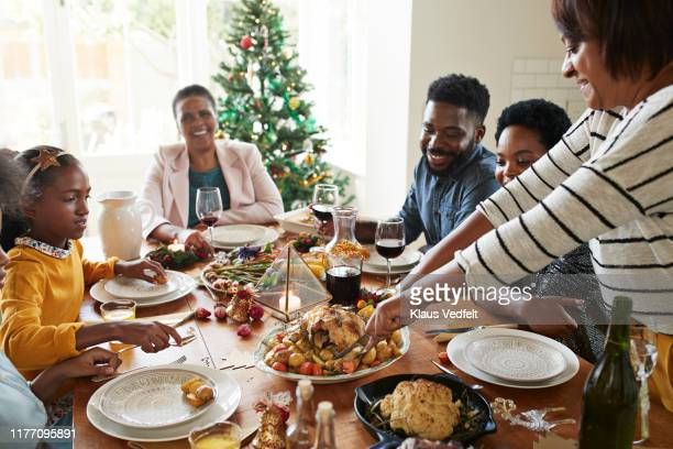 woman cutting meat for family and friends on table - christmas family stock pictures, royalty-free photos & images