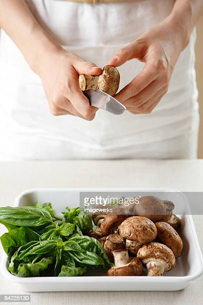 Woman cutting mushroom, mid section