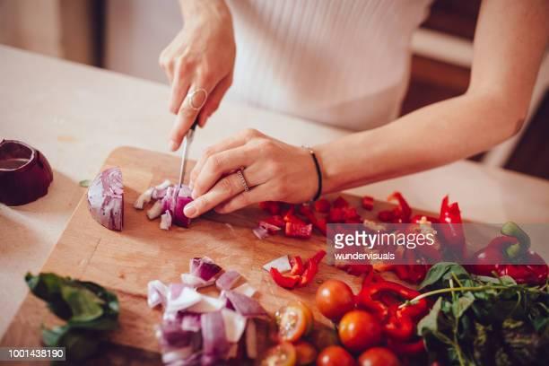frau schneiden zwiebeln und gemüse auf schneidebrett - zwiebel stock-fotos und bilder