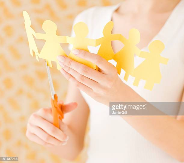 Woman cutting out paper dolls