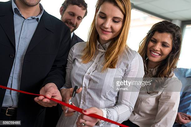 Woman cutting red ribbon with smiling onlookers beside.