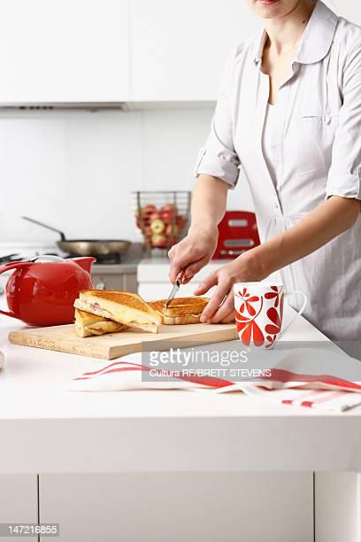 Woman cutting sandwiches in kitchen