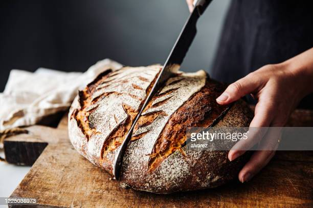 woman cutting sourdough bread with knife on board - loaf of bread stock pictures, royalty-free photos & images