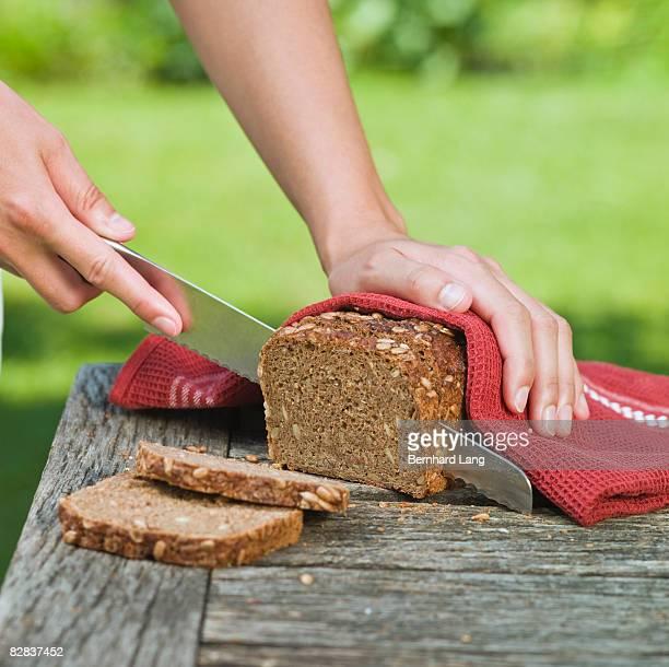 Woman cutting whole-grain bread