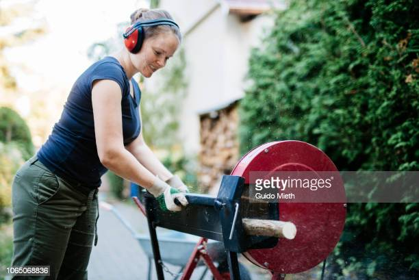 Woman cutting wood with a saw outdoor.