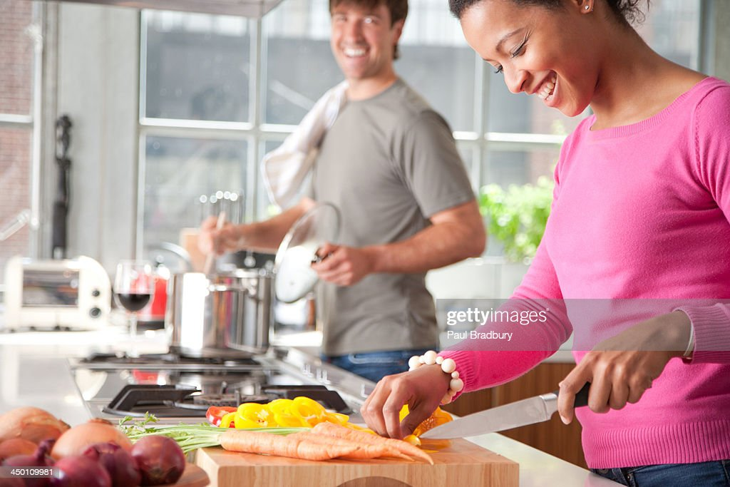 Woman cutting yellow peppers with man in background : Stock Photo