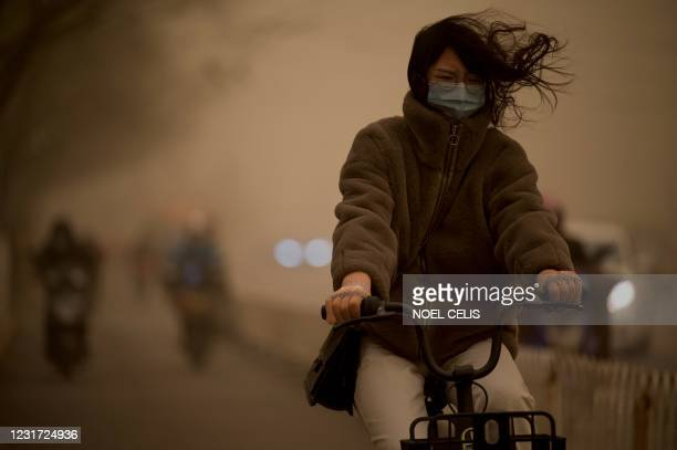 Woman cycles along a street during a sandstorm in Beijing on March 15, 2021.
