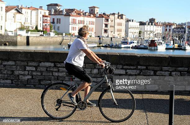 A woman cycles along the wharf in Ciboure with the port of SaintJeandeLuz in background southwestern France as the weather forecast predicts a...