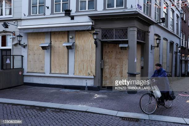Woman cycles her bike past a board-covered closed shop in Den Bosch, on January 26, 2021 a day, after police clashed with groups of demonstrators...