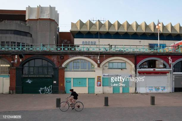 A woman cycles passed closed shops under the promenade on May 9 2020 in Brighton England There are numerous restaurants cafes and bars along the...