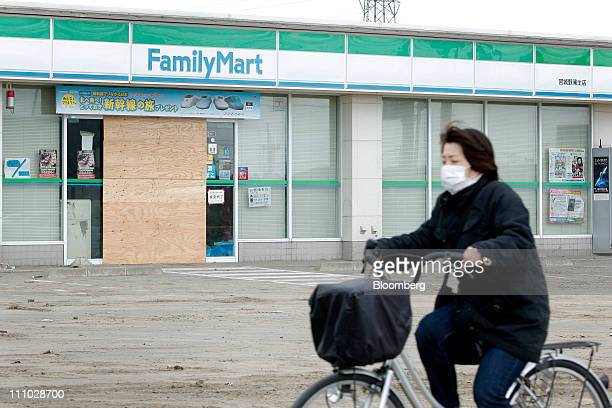 A woman cycles past a FamilyMart Co convenience store closed and damaged by the March 11 earthquake and tsunami in Sendai City Miyagi Prefecture...