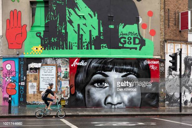 A woman cycles past a piece of street art by artist Jules Muck in collaboration with Global Street Art paying tribute to the late Aretha Franklin in...
