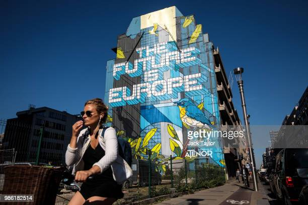 A woman cycles past a piece of street art by Belgian artist Julien Crevaels aka Novadead on the first day of the European Council leaders' summit on...