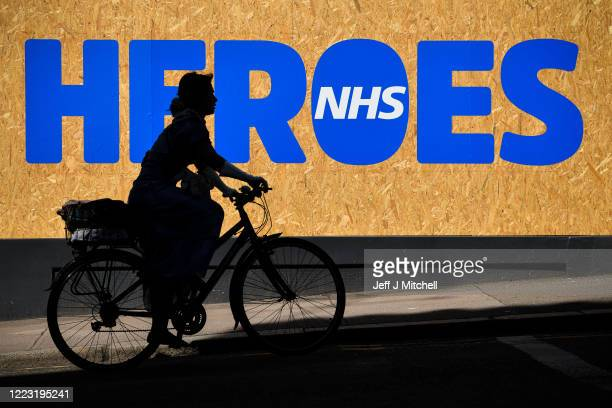 Woman cycles past a sign of support for the NHS during the coronavirus lockdown on May 6, 2020 in Glasgow, Scotland. The country continues quarantine...