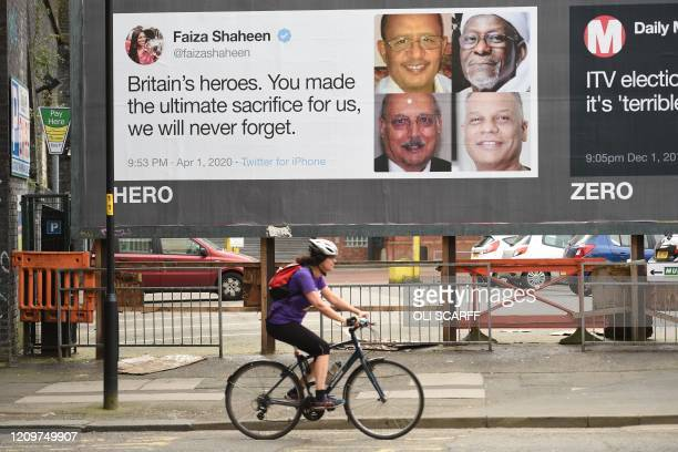 A woman cycles past posters critical of comments made by Brexit Party leader Nigel Farage in a neardeserted Manchester northwest England on April 12...