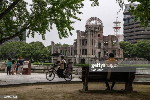 Woman cycles past the Atomic Bomb Dome on August 4, 2020 in Hiroshima, Japan. This Thursday will mark the 75th anniversary of the atomic bombing of...