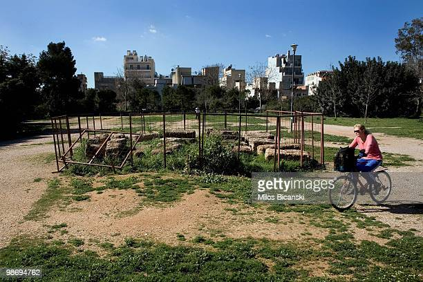 A woman cycles past the existing archeology of Plato's Academy the world's first university on March 9 2010 in Athens Greece Greece has requested...