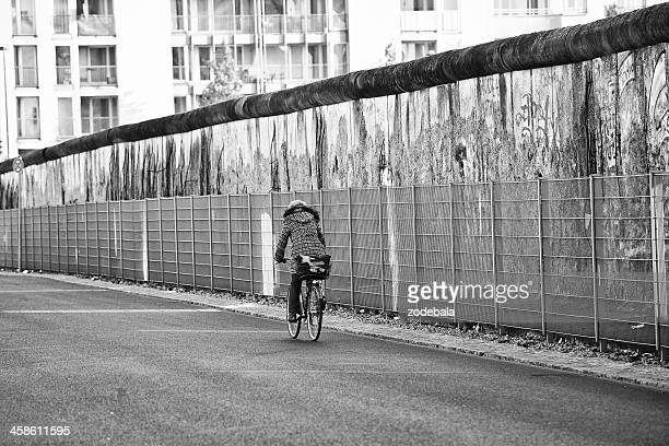 Woman Cycling Along the Ruins of Berlin Wall, Germany