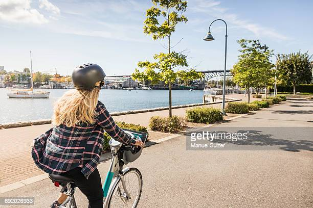 woman cycling along waterfront, vancouver, canada - vancouver canada stock pictures, royalty-free photos & images
