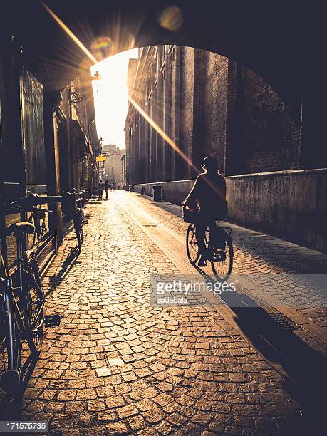 Woman Cycling at Sunrise in Ferrara, Italy