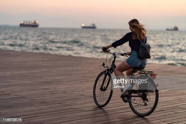 woman cycling by the sea - wide shot stock pictures, royalty-free photos & images