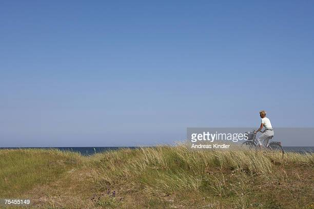 woman cycling by the sea. - one senior woman only stock pictures, royalty-free photos & images