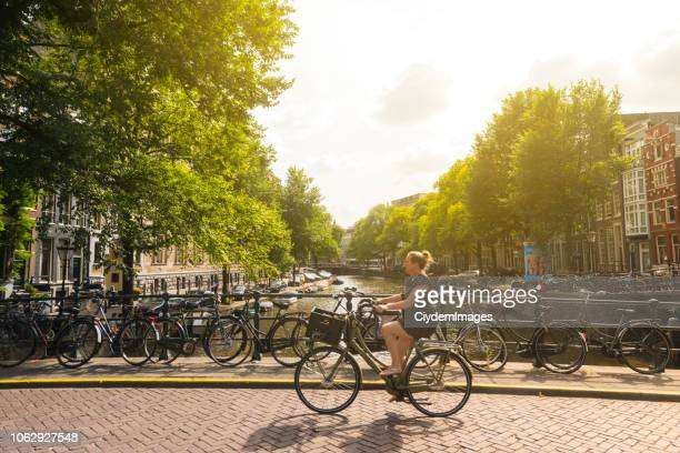 a woman cycling in amsterdam, netherlands - capital cities stock pictures, royalty-free photos & images