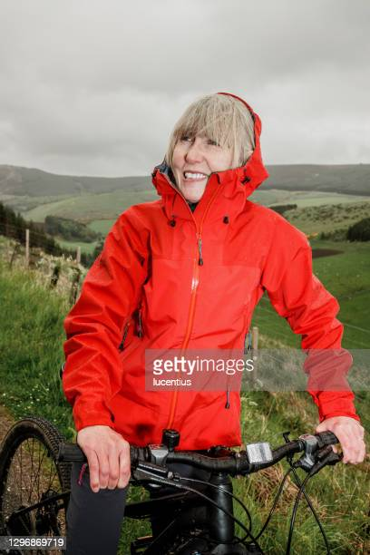 woman cycling in the rain - vertical stock pictures, royalty-free photos & images