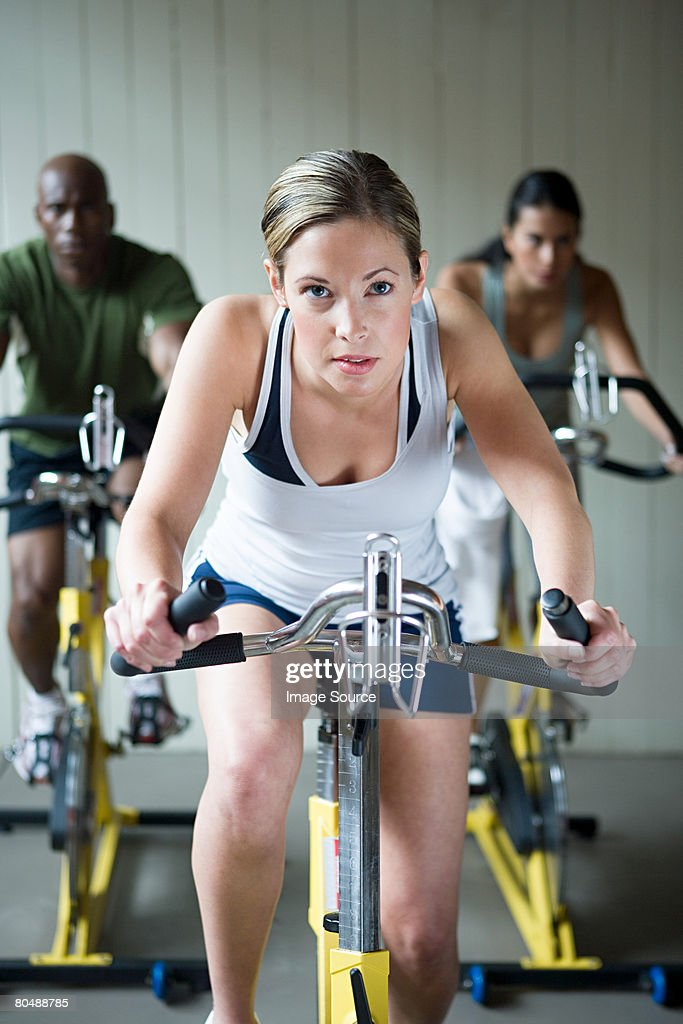 A woman cycling on an exercise bike : Stock Photo