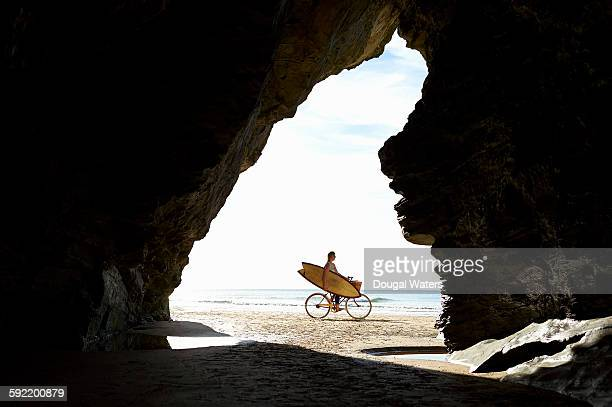 Woman cycling on beach holding surfboard.