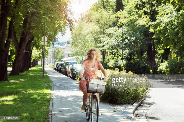 Woman cycling on bicycle in tree lined street, Innsbruck, Tirol, Austria, Europe