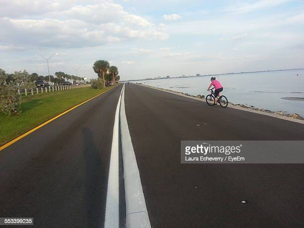 Woman Cycling On Road By Sea