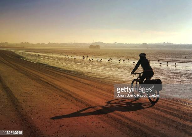woman cycling on sand at beach against sky during sunset - twilight stock pictures, royalty-free photos & images