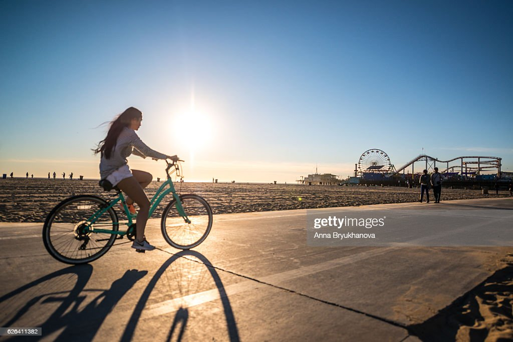 Woman cycling on Santa Monica beach, CA, USA : Stock Photo