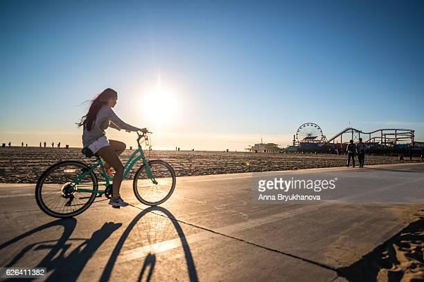 Woman cycling on Santa Monica beach, CA, USA