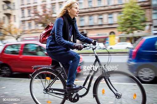Woman cycling on street in city during winter