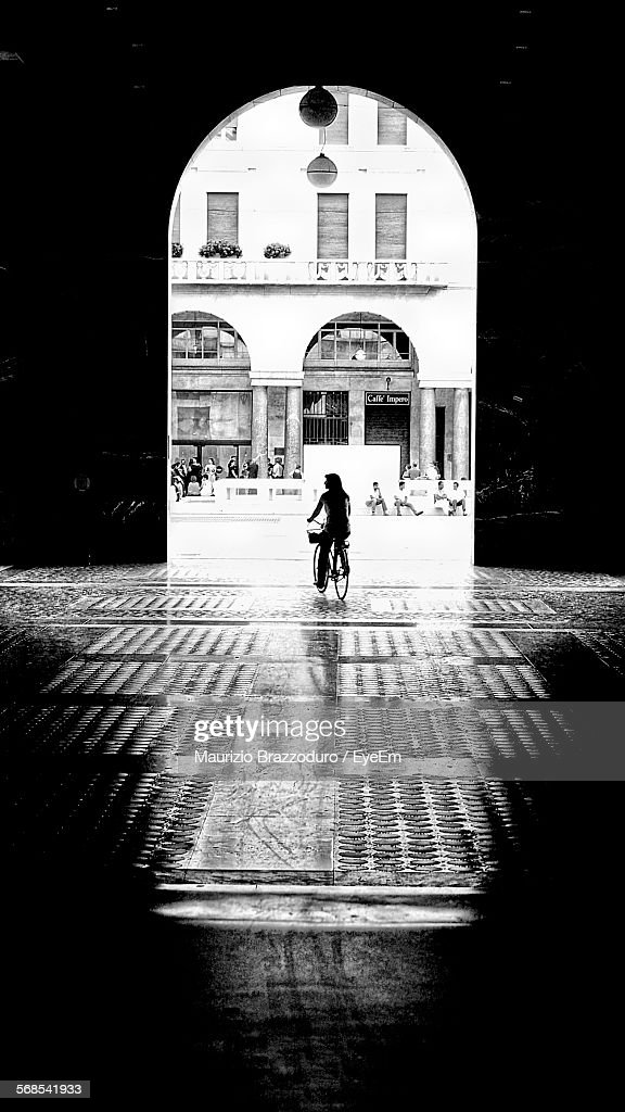 Woman Cycling On Street Leading Towards Archway : Stock Photo