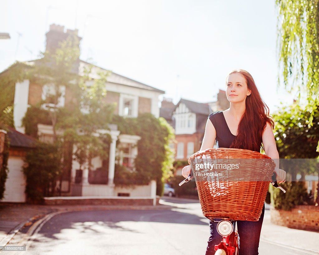 Woman cycling on streets on sunny day : Stock Photo
