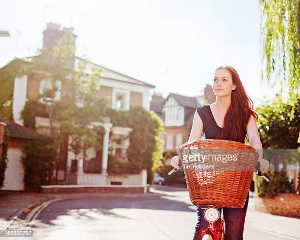 Woman cycling on streets on sunny day