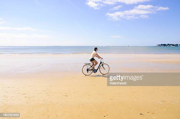 Woman cycling on the beach early in the morning