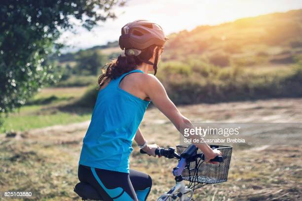Woman cycling on the mountains on a warm sunny day