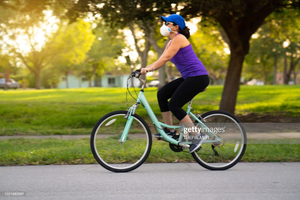 Woman cycling on the neighborhood : Stock Photo