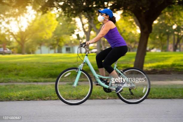 mulher pedalando no bairro - ciclismo - fotografias e filmes do acervo