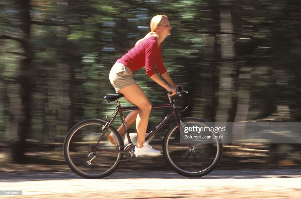 Woman cycling outdoors : Stock Photo