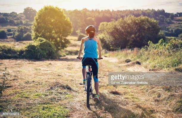 Woman cycling through nature on a sunny day