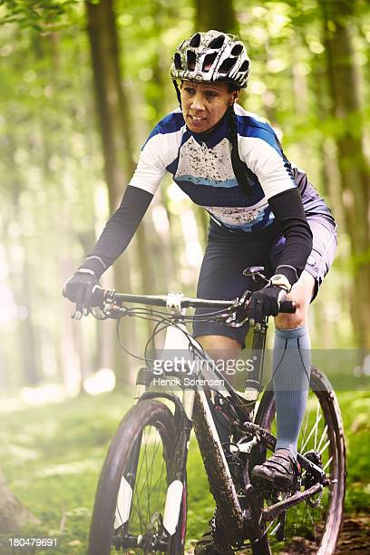 Woman cycling through the forest