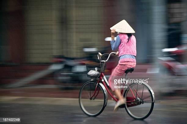 Woman Cycling Through The Rain In Nha Trang, Vietnam