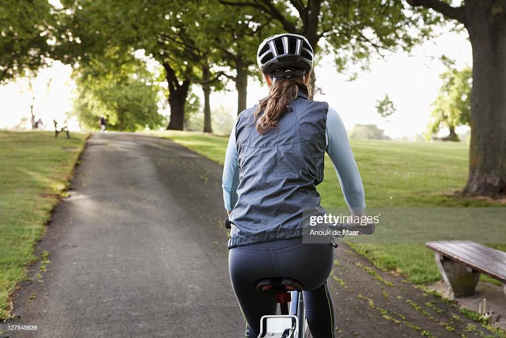 Woman cycling uphill at park : ストックフォト