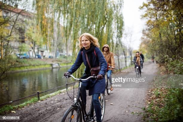 woman cycling with friends on road in winter - 45 49 years stock pictures, royalty-free photos & images